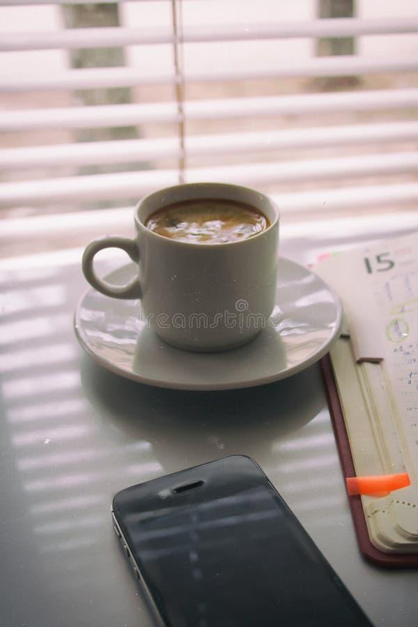 Schattenbilder des Sonnenaufgangmorgenkaffees mit einer Anmerkung und einem Telefon lizenzfreie stockbilder
