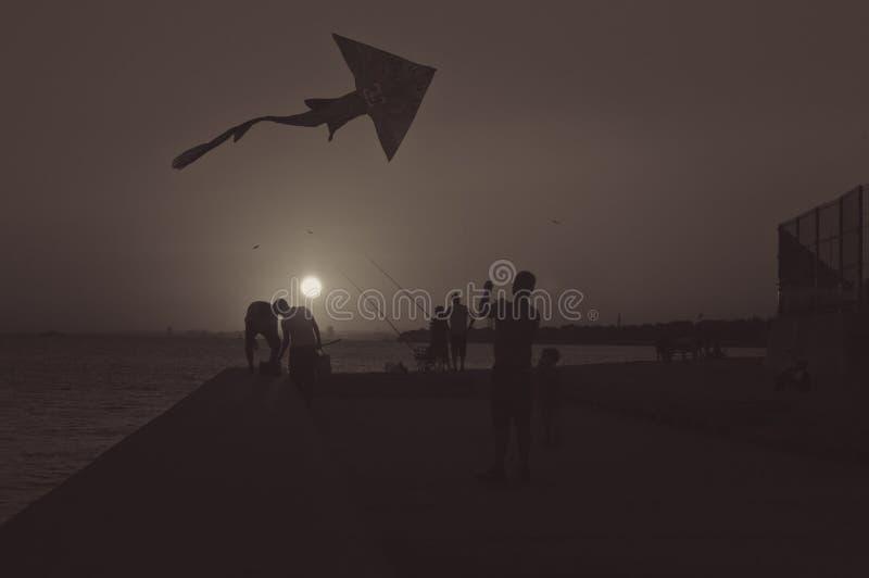 Schattenbilder des Vaters und des Sohns, die einen Drachen im Sonnenuntergang fliegen stockfotografie