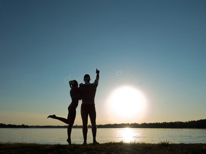 Schattenbilder eines liebevollen Paares auf dem Strand Sonnenuntergang auf dem Strand stockfotografie