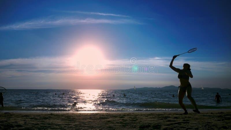 Schattenbilder Leute spielen Badminton auf dem Strand bei Sonnenuntergang lizenzfreies stockbild