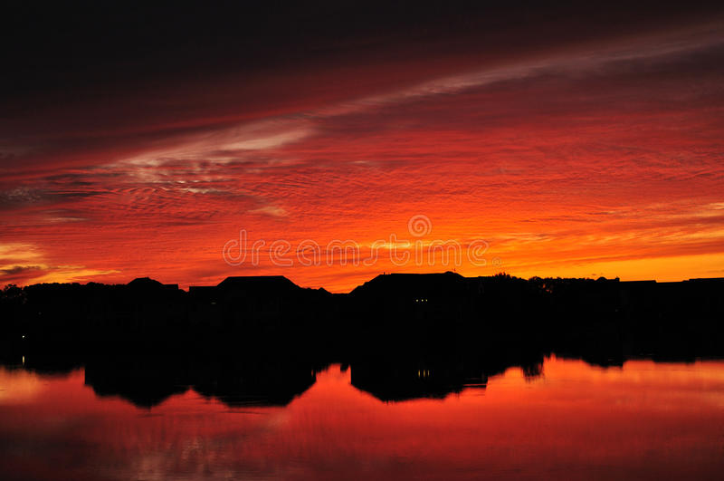 Schattenbilder u. Reflexionen der See-Häuser am Sonnenuntergang lizenzfreie stockfotos