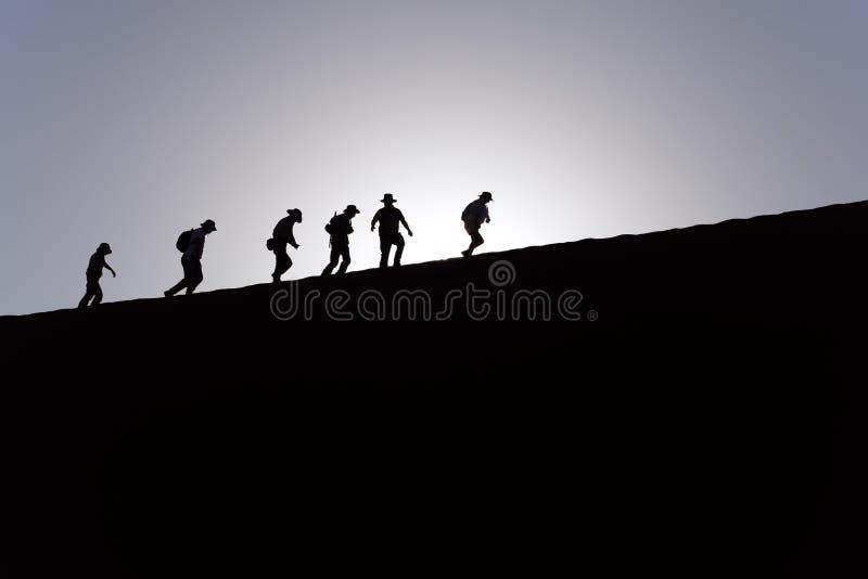 Schattenbilder u. Schatten von sechs Leuten, die oben eine hohe Sanddüne in Sossusvlei, Namibische Wüste, Namibia kurz nach Sonne stockbild