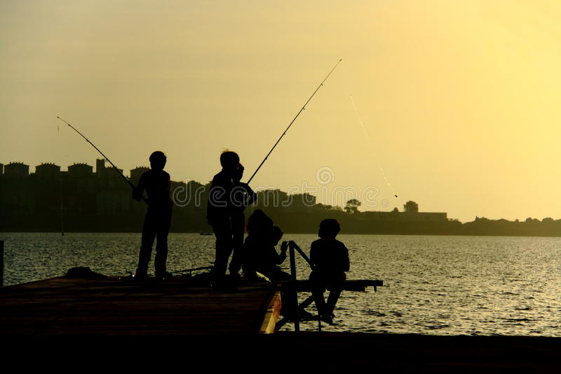 Schattenbilder von childs auf anziehenden Fischen des Piers lizenzfreie stockbilder