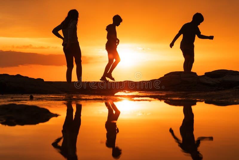Schattenbilder von den Kindern, die glücklich auf dem Strand bei Sonnenuntergang im Sommer spielen lizenzfreie stockbilder