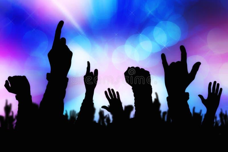 Schattenbilder von den Konzertpublikumhänden, die Band auf Stadium stützen lizenzfreie stockfotos