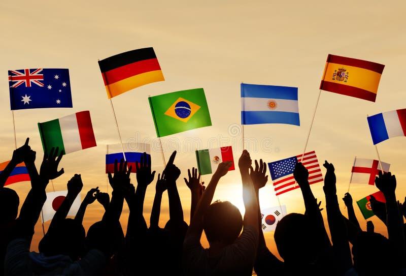 Schattenbilder von den Leuten, die Flaggen aus verschiedenen Ländern halten lizenzfreie stockfotografie