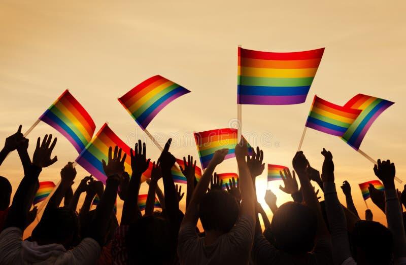Schattenbilder von den Leuten, die homosexuelle Pride Symbol-Flagge halten lizenzfreie stockfotografie