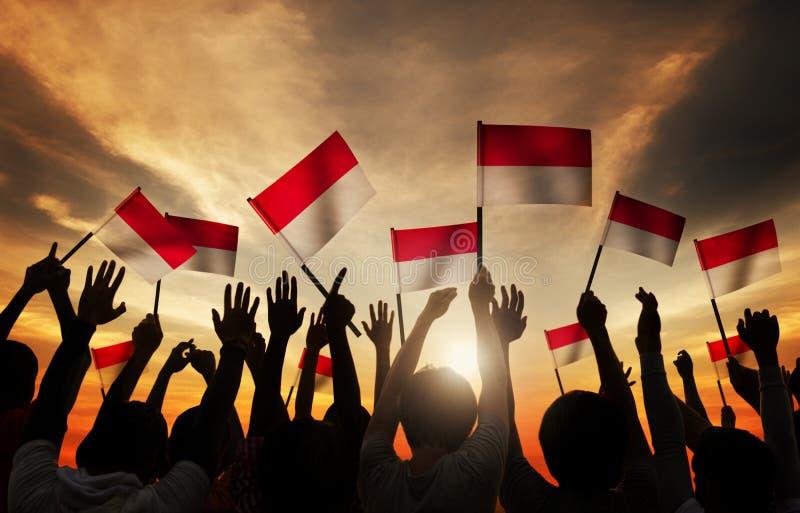 Schattenbilder von den Leuten, welche die Flagge von Indonesien halten lizenzfreies stockfoto