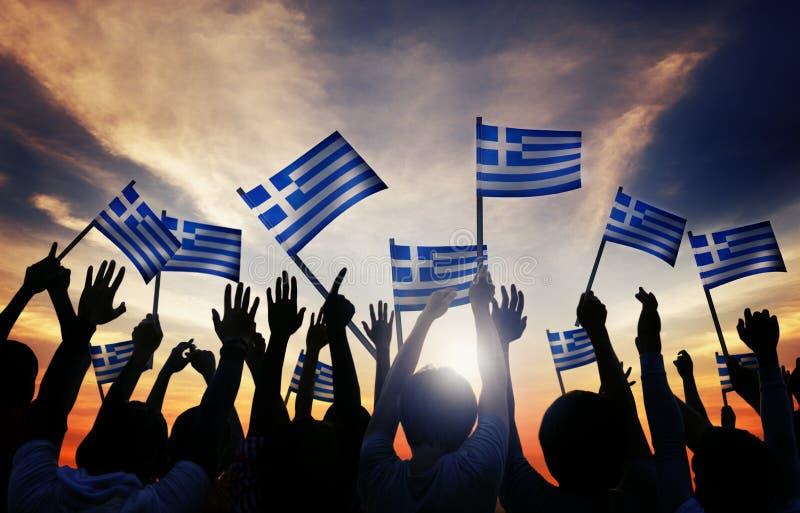 Schattenbilder von den Leuten, welche die Flagge von Griechenland halten lizenzfreie stockfotografie