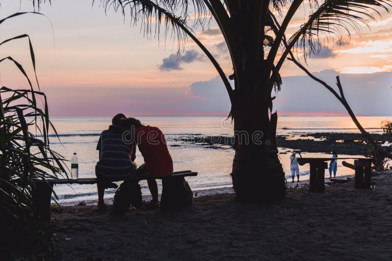 Schattenbilder von den liebevollen Paaren, die bei Sonnenuntergang durch das Meer sich umfassen stockfotos