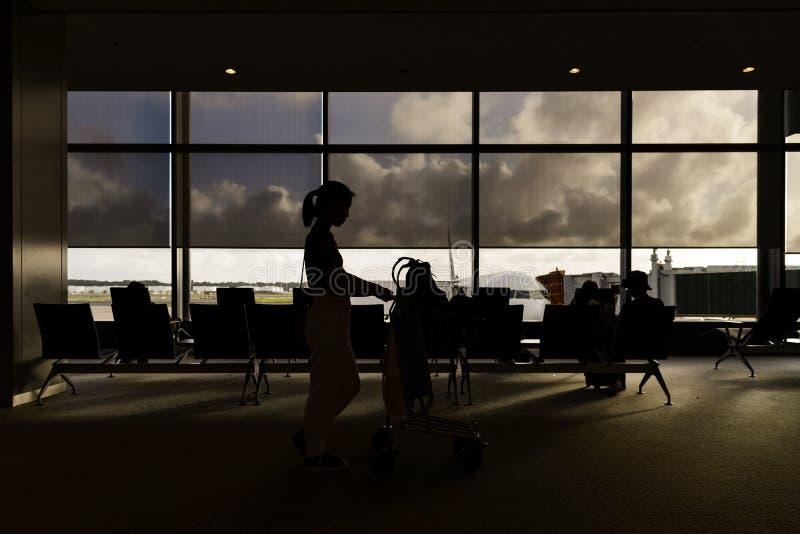 Schattenbilder von Frauen mit Gep?ckwagen im Flughafenabfahrtaufenthaltsraum stockbilder