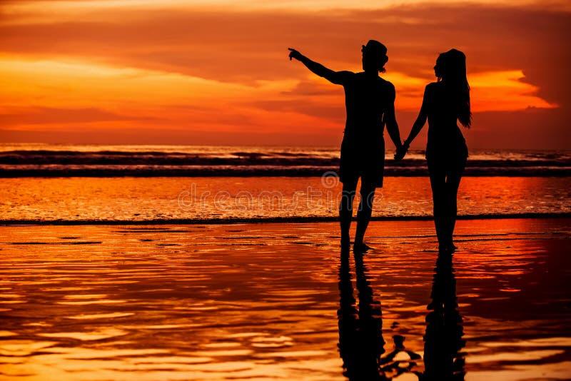Schattenbilder von jungen Paaren in der Liebe, die auf staing ist stockfotos