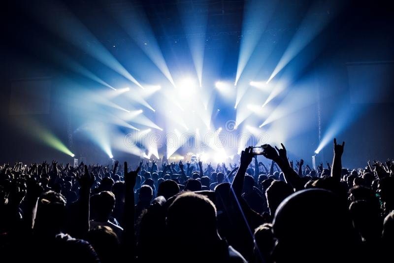 Schattenbilder von Leuten in einem hellen im Poprockkonzert vor dem Stadium Hände mit Geste Hörnern Das schaukelt Partei in a lizenzfreies stockfoto