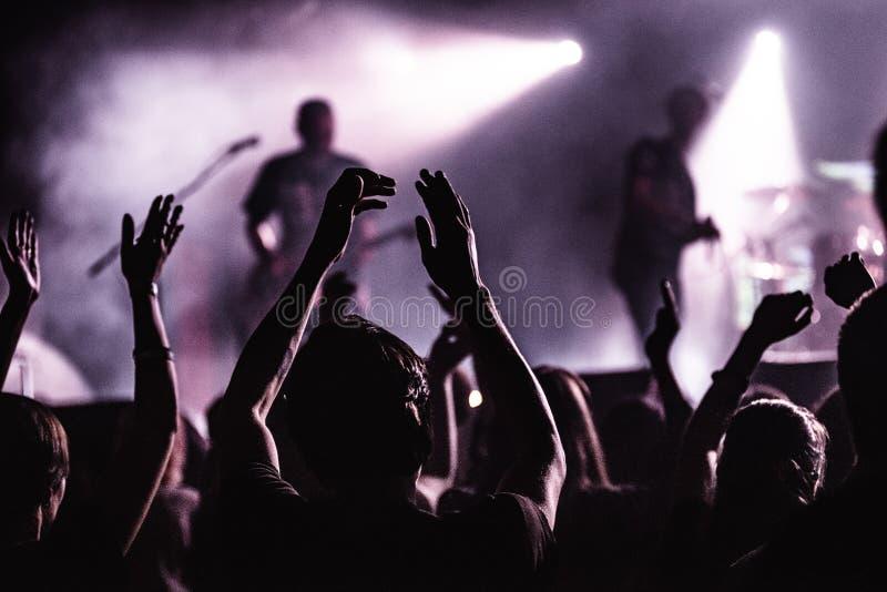 Schattenbilder von Leuten in einem hellen im Poprockkonzert vor dem Stadium Hände mit Geste Hörnern Das schaukelt Partei in a stockfotografie