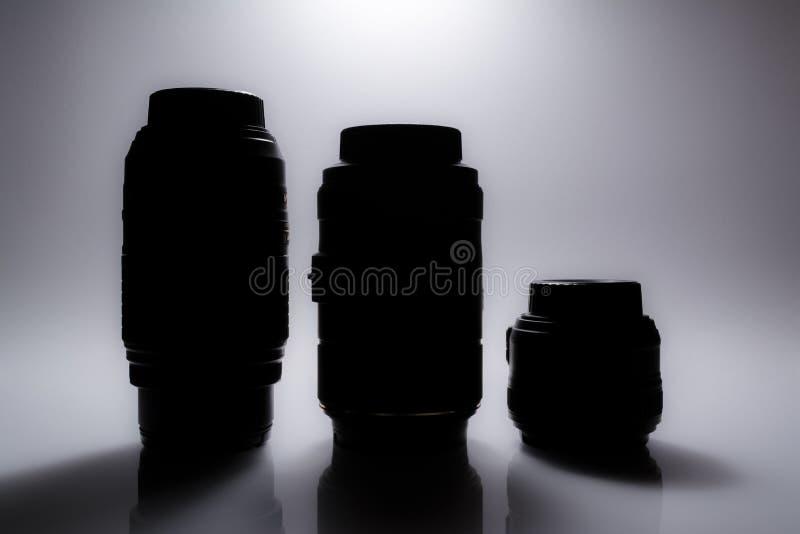 Schattenbilder von SLR-Kameraobjektiven mit Reflexion lizenzfreies stockbild