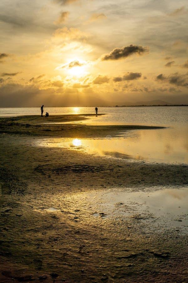 Schattenbilder von unerkennbaren Leuten auf dem Strand bei Sonnenuntergang mit dem ruhigen See stockfotos