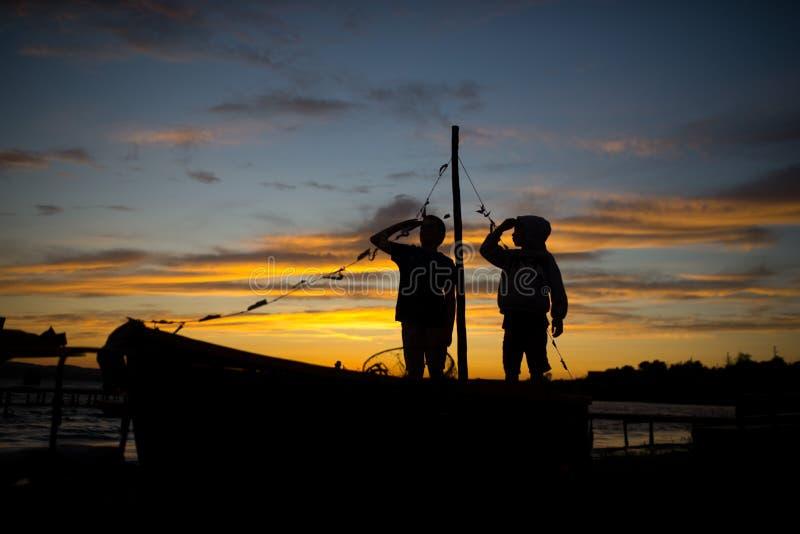 Schattenbilder von zwei Jungen, die in einem Boot bei Sonnenuntergang spielen stockfotografie