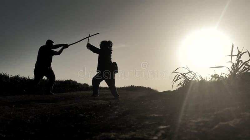 Schattenbilder von zwei Samurais, die mit Klingen in den Strahlen des Sonnenuntergangs kämpfen stockfotografie