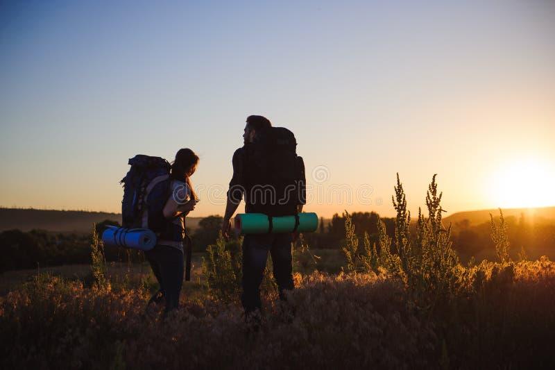 Schattenbilder von zwei Wanderern mit Rucksäcken gehend bei Sonnenuntergang Trekking und Genießen der Sonnenuntergangansicht stockfoto