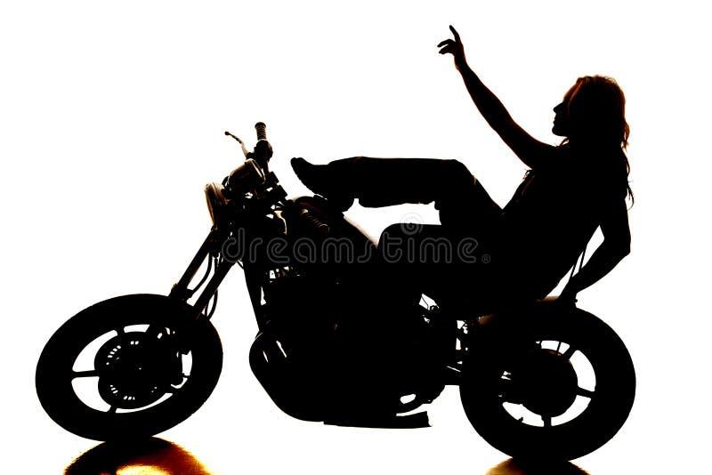 Schattenbildfrau auf Motorrad oben zeigend stockbild