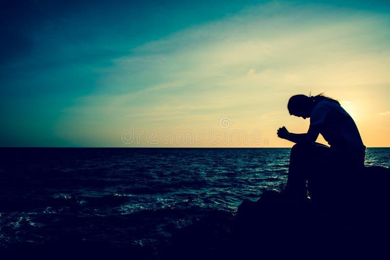 Schattenbildfrauen, die allein auf dem Felsen sitzen Psychische Gesundheit, stockbild