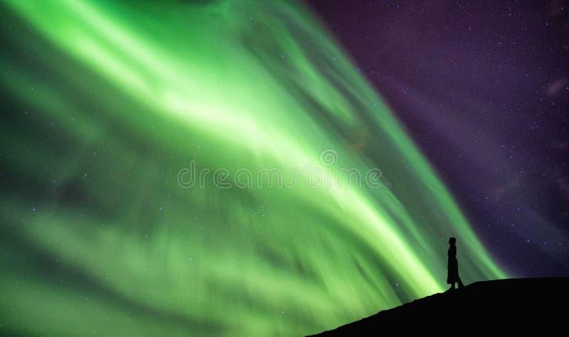 Schattenbildfrauenstellung auf Klippe mit aurora borealis-Tanzen stockfotografie