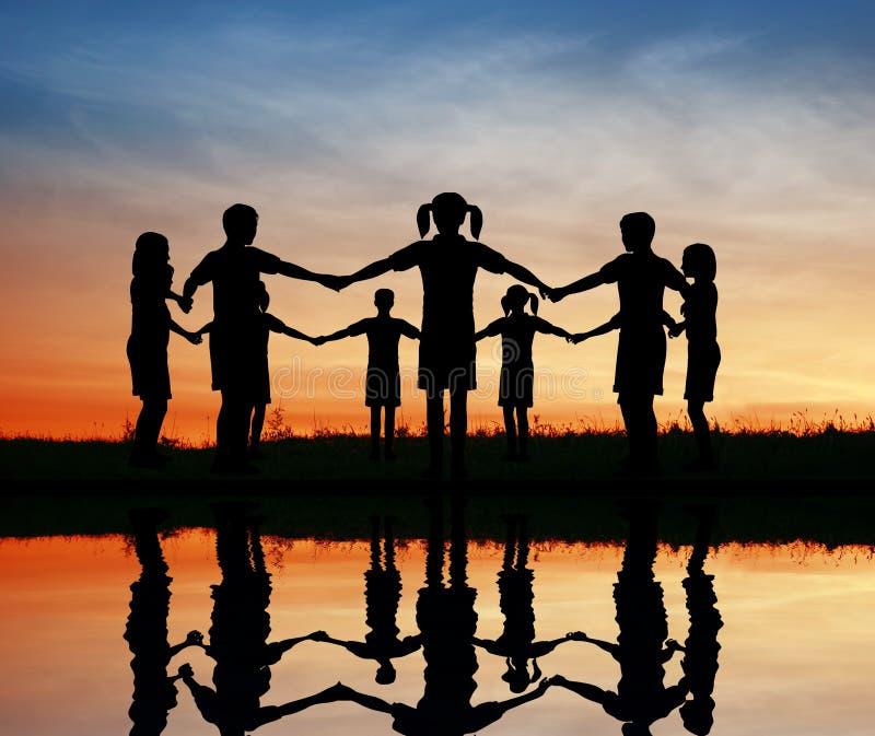Schattenbildkinder. Sonnenuntergangteich. lizenzfreies stockbild