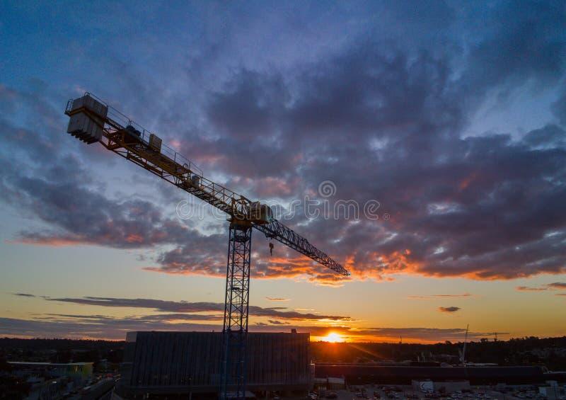 Schattenbildkran-Bauturm bei Sonnenuntergang stockfoto