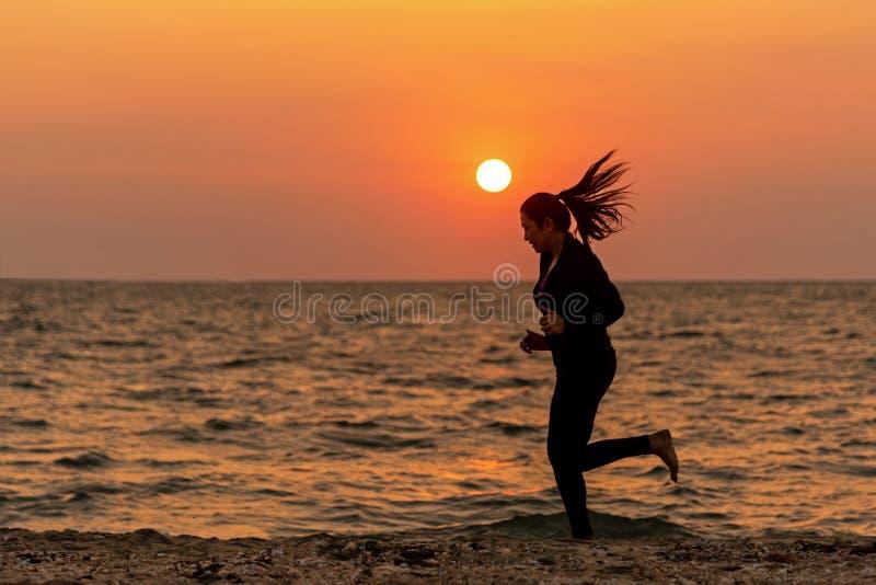 Schattenbildläuferfüße, die auf dem Strand im Sonnenuntergang im Freien laufen Asiatische Eignung und sportliche Frau, die für ge lizenzfreie stockfotografie