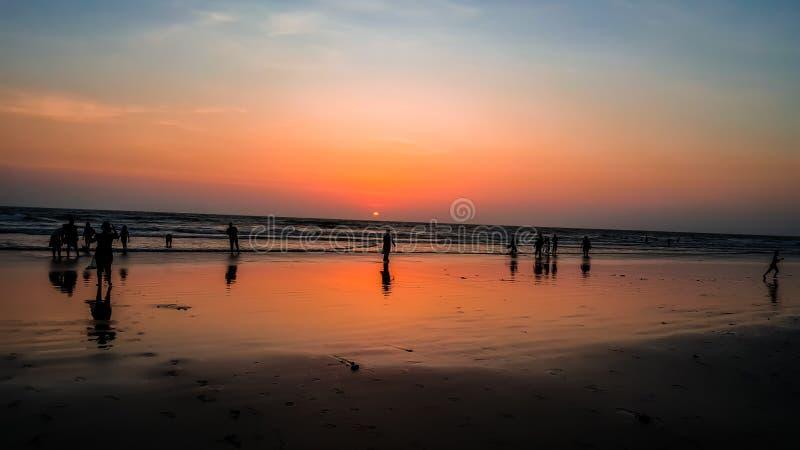 Schattenbildleute, die Sonnenuntergang an karde Strand Konkan-Maharashtra genießen stockfotos