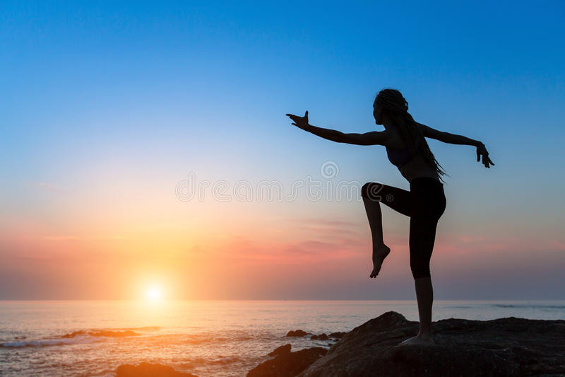 Schattenbildmädchen zieht in einen Tanz auf dem Ufer des Meeres während der Dämmerung um stockbilder
