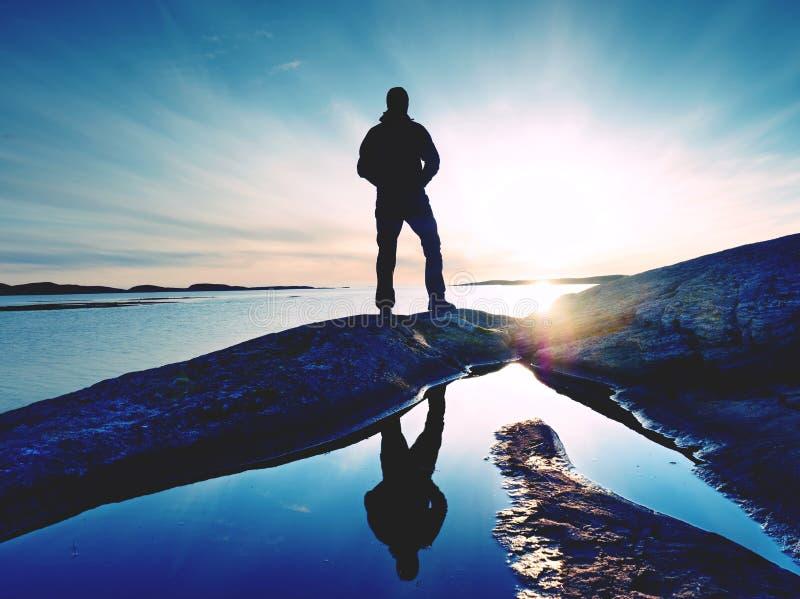 Schattenbildmann auf Klippe über Meer Touristischer Stand allein auf Felsen- und Uhrseehorizont stockfoto