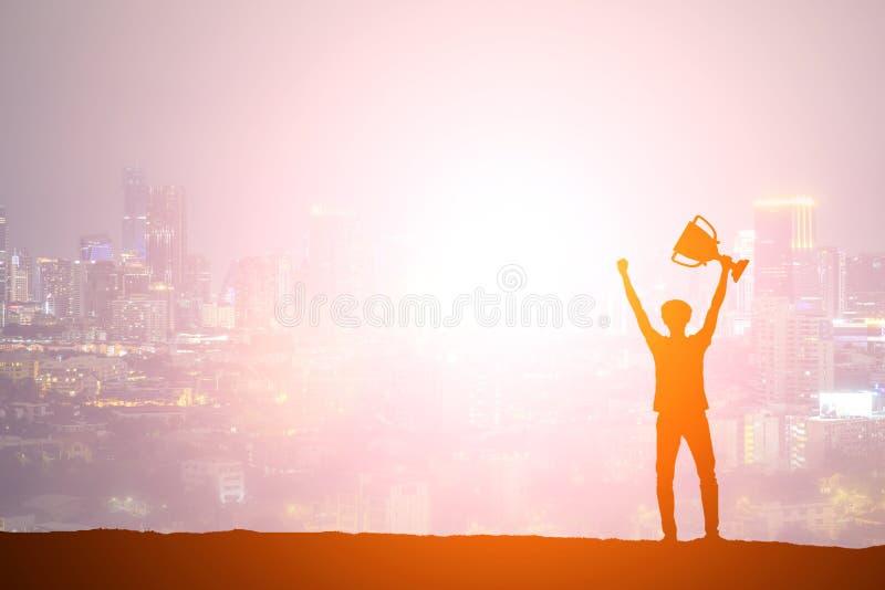 Schattenbildmann, der einen Goldtrophäencup als Sieger in COM hält stockfotografie
