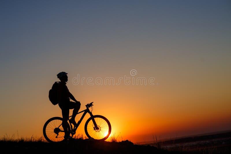 Schattenbildmannstand mit Mountainbike auf der Wiese stockbild