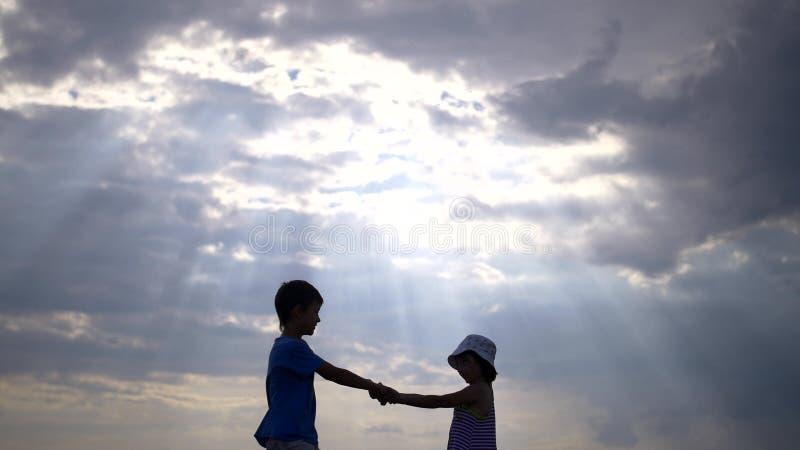 Schattenbildpaarkinder kreisen Händchenhalten gegen den Himmel bei Sonnenuntergang ein lizenzfreie stockfotos