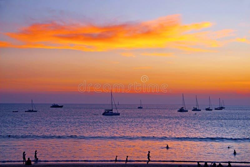 Schattenbildyachten und -leute bei Sonnenuntergang lizenzfreie stockbilder