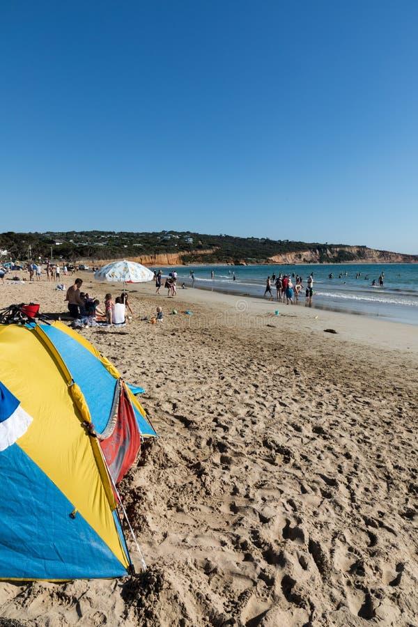 Schattenschutz auf einem gedrängten Strand im Sommer als Leuten genießen, im Ozean und im Sand zu schwimmen und zu spielen stockbilder