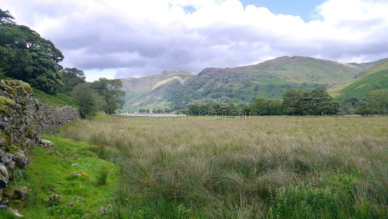 Schauen über Feld zu den Bergen lizenzfreies stockbild