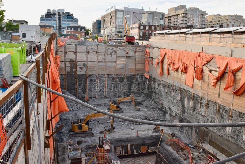 Schauen des tiefen Abstiegs zu den Grundlagen eines anderen Toronto-Hochhauses stockbilder