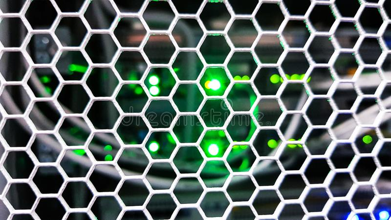 Schauen durch Bienenwabenmustert?ren innerhalb des modernen gro?en Datenservergestells im Rechenzentrum mit Netzwerk-Server-Hardw stockbild