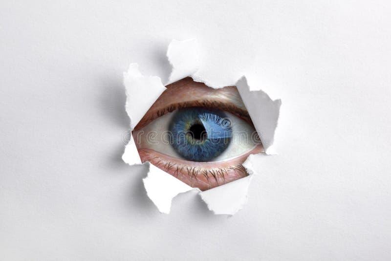 Schauen durch ein Loch im Weißbuch lizenzfreie stockfotos