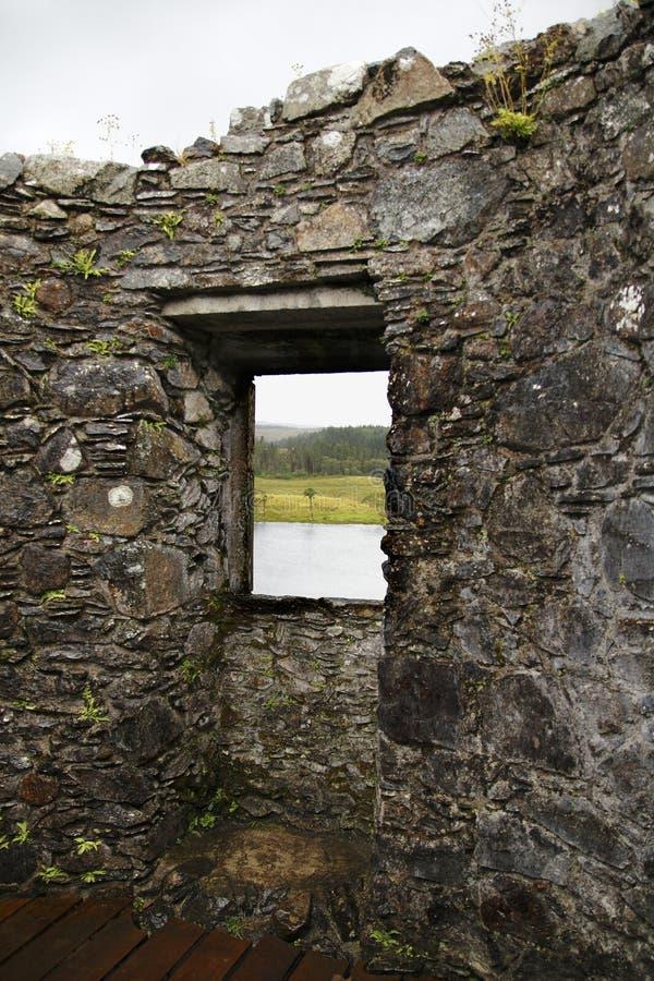 Schauen Sie durch ein Fenster von Kilchurn-Schloss, in der Loch Ehrfurcht auf einem einsamen Baum in den Hochländern von Schottla stockbilder