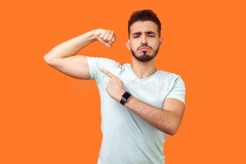 Schauen Sie sich meine Stärke an Porträt eines stolzen, ansehnlichen Brunette-Mannes, der auf Biceps zeigt Innenstudio isoliert a stockfotografie