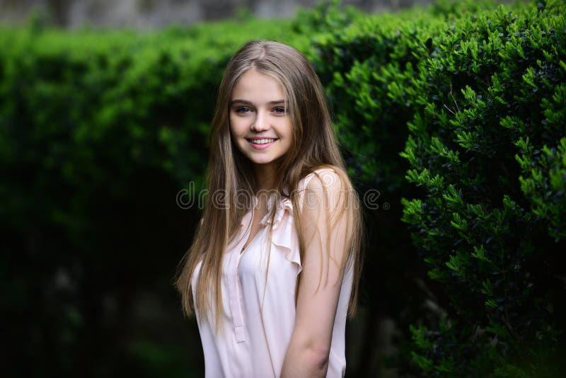 schauen Sie vom Mädchen nahe Grünpflanzen Sommer oder Frühlingsmode und -schönheit Mädchen in der zufälligen Kleidung im Freien S lizenzfreies stockfoto