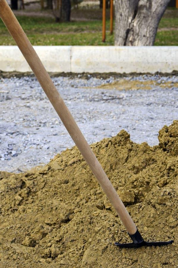 Schaufel des erfahrenen Arbeiters gehaftet in einen Sandhaufen an einer Baustelle lizenzfreie stockfotos