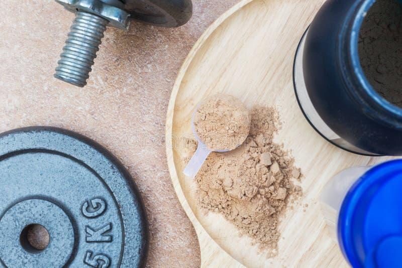 Schaufel des Molkeproteins auf einer hölzernen Platte mit Glas stockfotos