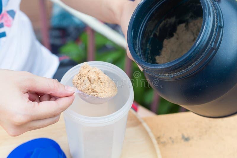 Schaufel des Molkeproteins auf einer hölzernen Platte mit Glas lizenzfreies stockbild