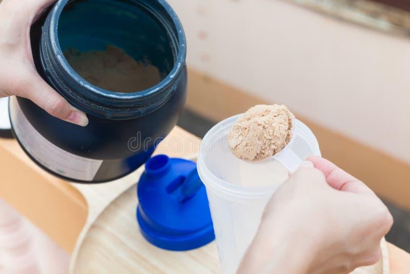 Schaufel des Molkeproteins auf einer hölzernen Platte mit Glas stockbilder