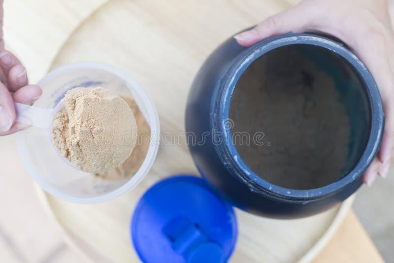 Schaufel des Molkeproteins auf einer hölzernen Platte mit Glas auf Draufsicht lizenzfreies stockbild