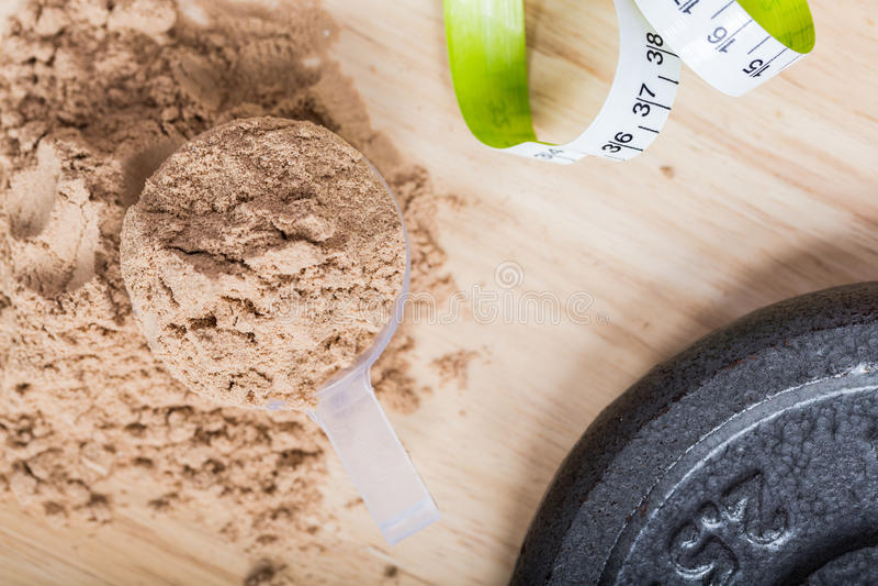 Schaufel des Molkeproteins auf einer hölzernen Platte mit Maßband stockfoto